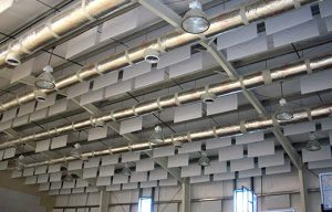 white acoustic sound baffles controlling excessive noise levels in a natatorium