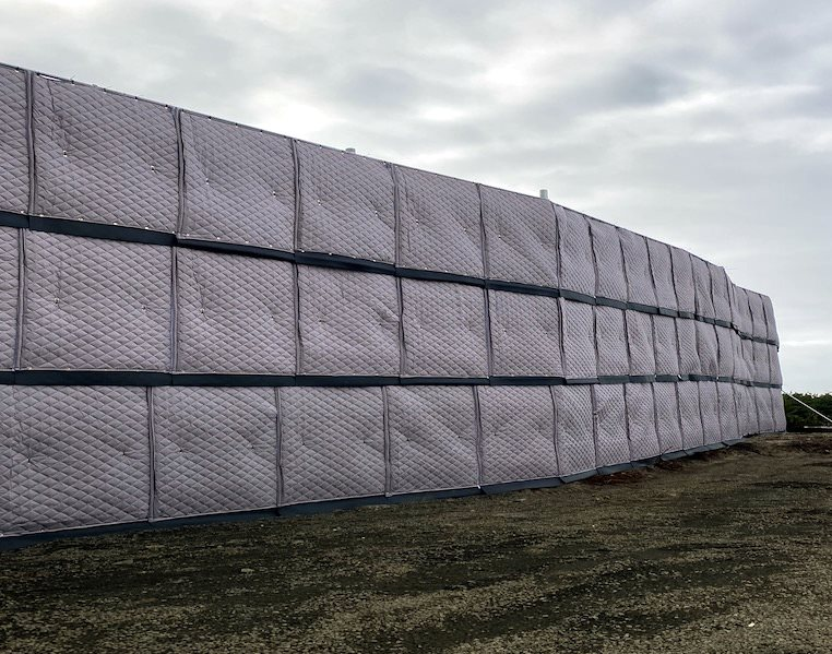 outdoor sound blankets attached to fence